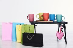 Black wooden tray with colorful cups and book on it sweat pink heart and shopping bags on white background, copy space. Black wooden tray with colorful cups and Stock Photography