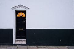 Black wooden Victorian door on a black and white wall Royalty Free Stock Photo