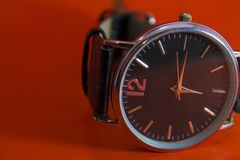 Wrist watch black on an orange background stock photos