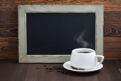 Black writing board and coffee with steam on wooden table Stock Images