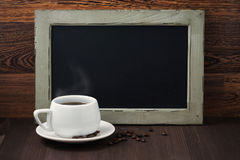 Black writing board and a cup of coffee with steam Stock Photography