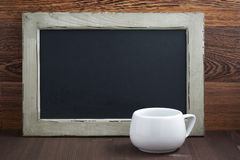 Black writing board and white cup Royalty Free Stock Photo