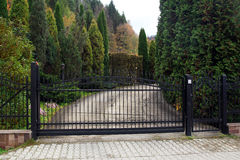 Black wrought gate to property with garden in the background royalty free stock photo
