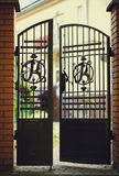 Black wrought iron and brick entrance gates. With home facade in background stock photo