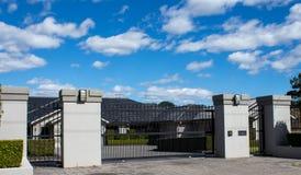 Black metal driveway entrance gates set in brick fence. Black wrought iron driveway entrance gates set in brick fence Royalty Free Stock Photo