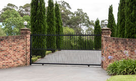 Black wrought iron driveway entrance gates set in brick fence. Black metal driveway entrance gates set in brick fence with trees in background Stock Images