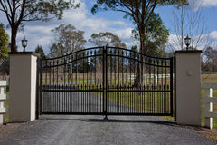 Black wrought iron entrance gates. Large black wrought iron entrance gates to farm property with trees and blue sky Royalty Free Stock Images