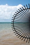 Black wrought iron fence design. Half circular black wrought iron metal artwork with Gulf of Mexico background royalty free stock photo