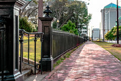 Black wrought iron fence next to sidewalk. Back wrought iron fence next to a red brick sidewalk in the city of Montgomery, Alabama Stock Photo