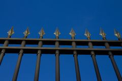 Black wrought iron fence with peaks on blue background stock photography