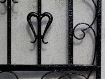 Black wrought iron gate detail against white stucco wall. Black wrought iron gate detail against textured white stucco wall stock photos