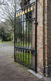 Black wrought iron gate with golden decorations. Opened black wrought iron gate with golden decorations at the entrance of a park-like estate with a castle in royalty free stock photos