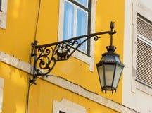 Black wrought iron wall lantern on a yellow wall. Royalty Free Stock Image