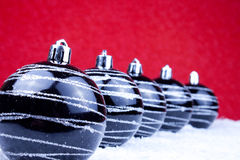 Black xmas balls in line. On snow with red background Stock Photo
