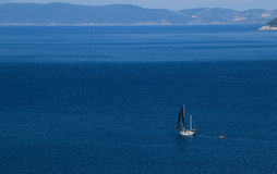 Black Yacht with black sales in the blue sea. One Yacht with black sales in the medeteranian blue sea near the cost of Elba in italy Stock Image