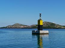 A black and yelllow beacon in the Adriatic sea Royalty Free Stock Photography