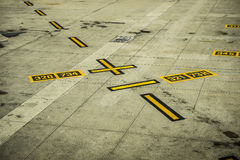 Black and yellow airport markings on concrete Royalty Free Stock Photo