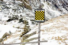 Black and Yellow avalanche risk warning sign in the mountains Royalty Free Stock Image