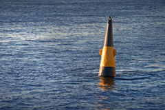 Black and yellow buoy. Floating conical black and yellow river buoy Royalty Free Stock Image