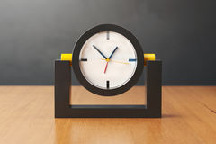 Black and yellow clock on a wooden table. 3D illustration. Table clock of black and yellow plastic on a light wooden table. White clock face with black, yellow Stock Image
