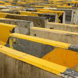 Black and yellow concrete road barriers or road blocks. Expressing endless barriers concept Stock Photos