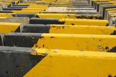 Black and yellow concrete road barriers or road blocks. Expressing endless barriers concept Stock Images