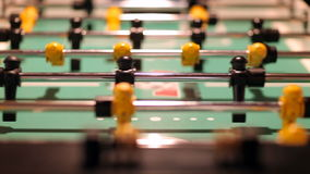 Black and Yellow Foosball Game. Rack focus shot of black and yellow teams play on a Foosball table. Person comes into frame and changes the score stock footage