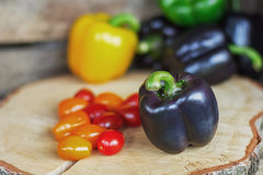 Black, yellow, green paprika`s and cherry tomatoes on a disk of birch wood. Royalty Free Stock Images