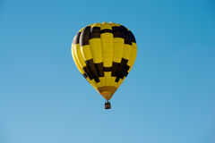 Black and yellow hot air balloon in a blue sky Stock Photography