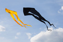 Black and yellow kites flying in the cloudy sky. Summer concept Royalty Free Stock Images