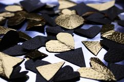 Many foil hearts of golden and black color on the table stock photography
