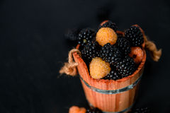 Black and yellow raspberries in a wooden basket on   background. Frame. Copy space. Top view. Black and yellow raspberries in a wooden basket on black wooden Stock Images