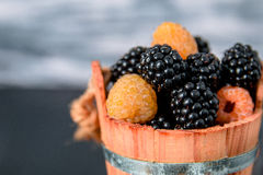 Black and yellow raspberries in a wooden basket on grey  background. Close up. Black and yellow raspberries in a wooden basket on grey wooden background. Close Stock Images