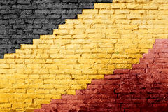 Black, yellow and red painted brick wall. Diagonal stripes Stock Photography