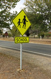 Black and yellow School sign with schoolground in background Royalty Free Stock Images