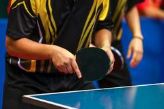 Black yellow shirt men playing double table tennis royalty free stock photo
