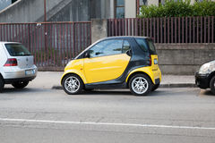 Black and yellow Smart car parked on urban roadside Royalty Free Stock Photos