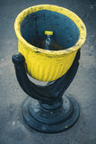 Black and yellow steel rubbish bin on the street. Close up. In the urn empty plastic bottle with yellow cap Stock Images