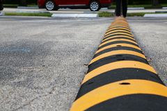 Striped Speed Bump. A black and yellow striped speed bump in a parking lot alerts drivers to slow down as a red minivan drives on the street in the background royalty free stock images