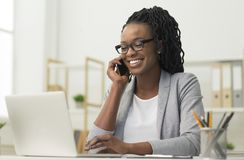 Free Black Young Lady Having Phone Conversation Sitting At Workplace Royalty Free Stock Image - 160048966