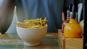 Black young man enjoys a snack. Unrecognizable young adult male enjoys a savoury salty snack with sea salt french fries in a trendy food joint, purchased from a stock video footage