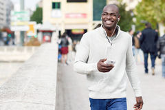 Black young man with a smartphone in his hand in urban backgroun Stock Images