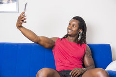 Black young man taking selfie photo on sofa. Handsome black muscular bodybuilder man taking selfie with cell phone while laying on couch Stock Photo
