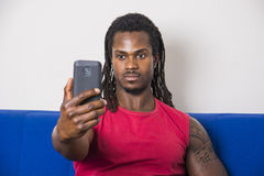 Black young man taking selfie photo on sofa. Handsome black muscular bodybuilder man taking selfie with cell phone while laying on couch Stock Photos