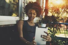 Black young teenage female is reading electronic book. Thoughtful young biracial female is holding digital tablet while sitting on the bench near summer house Stock Images