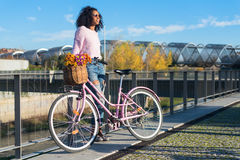 Black young woman riding a vintage bicycle stock images