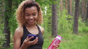 Black young woman using smartphone after jogging and shows green screen to the camera in slow motion