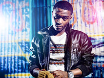 Black youth with jacket and colorful lights Stock Photo