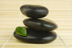 Black zen pebbles and green leaf on bamboo. Balanced black zen pebbles and a young green leaf on bamboo mat. Alternative therapy and new life symbol stock image