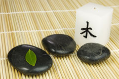 Black zen pebbles, green leaf and japanese candle. Black zen pebbles, japanese candle and a young green leaf on bamboo mat. Alternative therapy and new life stock photography